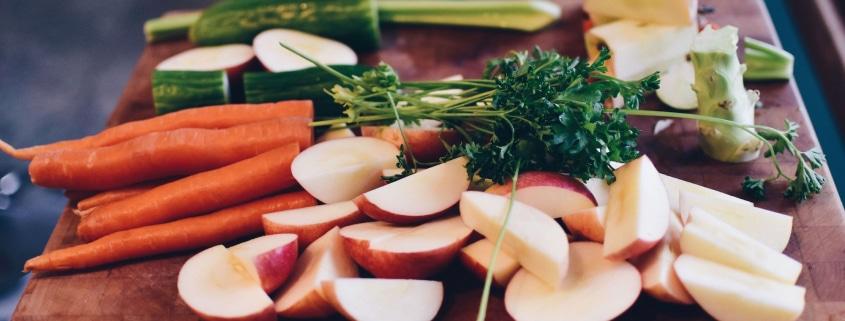 Bio-Lebensmittel: Geschnittene Äpfel, Karotten und Gurken auf einem Holzbrett