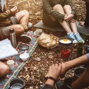Menschen frühstücken vor einem Zelt