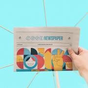 Eine Hand hält eine Zeitung mit der Überschrift Good News vor blauem Hintergrund