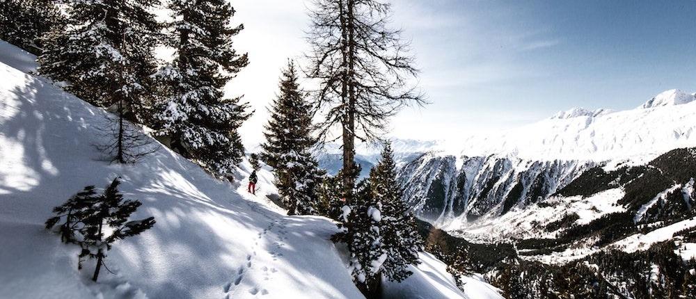 Schneeschuhspuren im Schnee an einem Hang