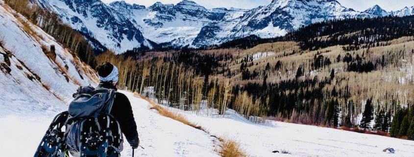 Ein Mensch mit Schneeschuhen am Rucksack wandert durch winterliche Landschaft