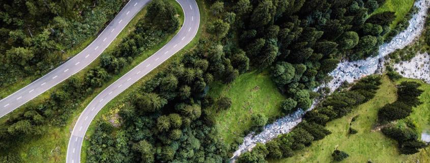 Luftansicht: Leere Straße, ein Fluss und Wald