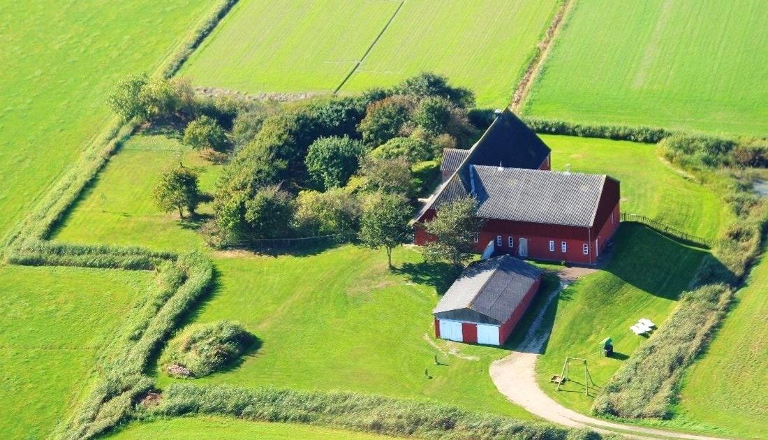 Eine rote Norseeinselfarm umrandet von Feldern von oben