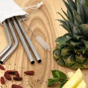 Edelstahlstrohhalme in Leinenbeutel auf einem Tisch mit Ananas