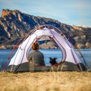 Frau und Hund in einem Zelt am See