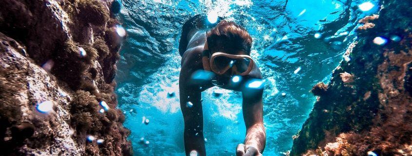 Eine Person mit Taucherbrille unter Wasser