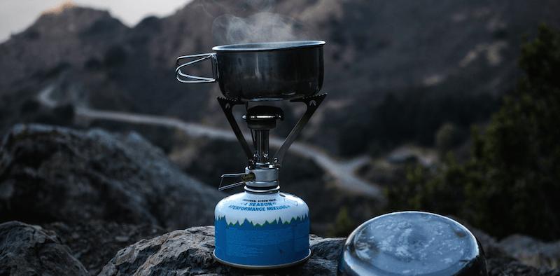 Camping-Kocher vor einer Bergkulisse