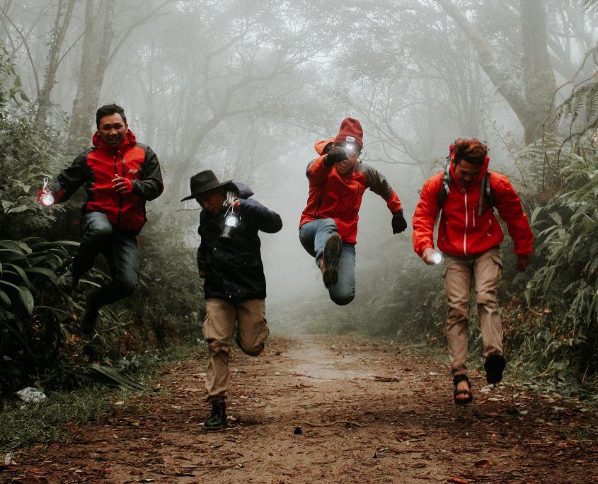 Vier Menschen in Regenjacken springen durch den Wald
